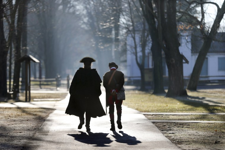 Image: Revolutionary War re-enactors walk along a path before the re-enactment of Gen. George Washington's Christmas Day crossing