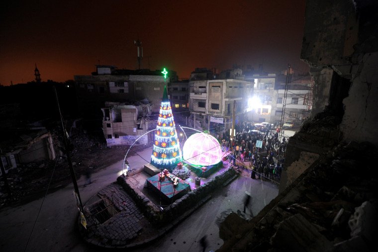 Image: People gather by a Christmas tree near damaged buildings during Christmas eve in al-Hamidiyah neighbourhood in the old city of Homs