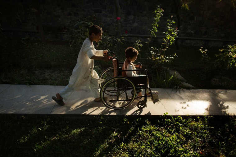 Image: Ajmal, 11, pushes Sangeer, 7, through the garden at Emergency Surgical Center