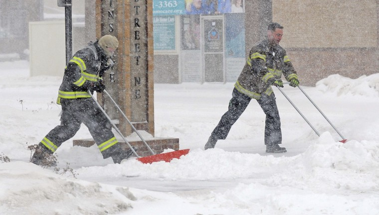 Mandan firefighters Shane Weltikol, left, and Chad Nicklos clear accumulating snow from outside the firehouse in downtown Mandan, N.D., as the Christmas Day blizzard intensifies on Sunday, Dec. 25, 2016.