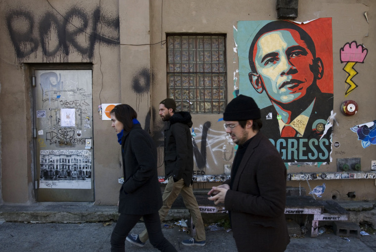 Image: People walk past a campaign poster for Democratic presidential candidate Barack Obama
