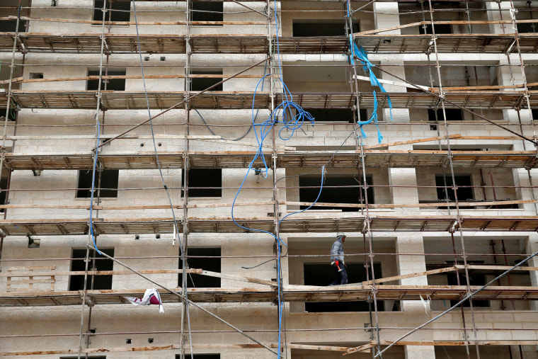 Image: A worker walks on scaffoldings in a construction site at the Israeli settlement of Har Homa, in the occupied West Bank