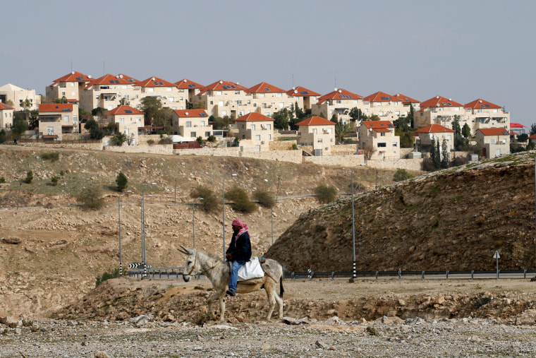 Image: A Palestinian man rides a donkey near the Israeli settlement of Maale Edumim, in the occupied West Bank