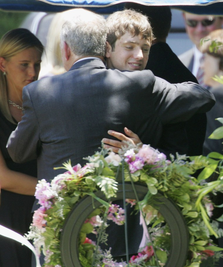 In this June 29, 2006, file photo, John Ramsey hugs his son, Burke, facing the camera, at the graves of his wife, Patsy, and daughter JonBenet, during services for his wife at the St. James Episcopal Cemetery in Marietta, Ga. Burke Ramsey is suing CBS and others for $750 million over a series that aired in September 2016 that Ramsey alleges concluded he killed his sister.