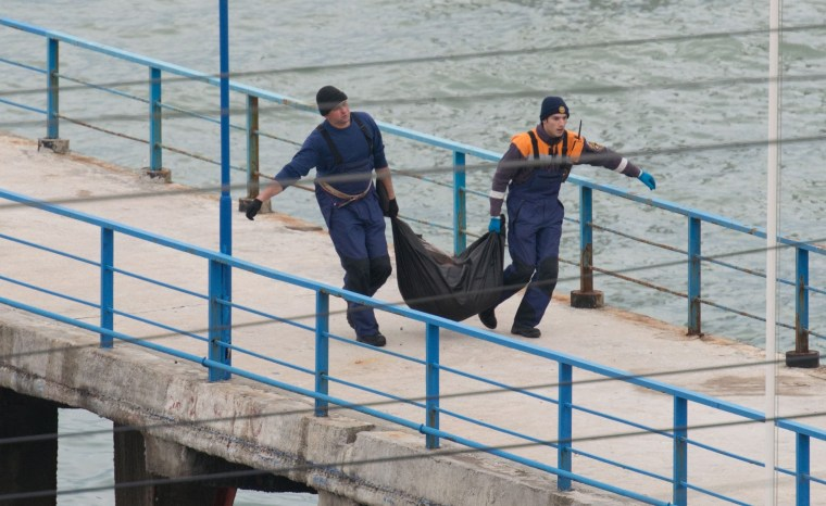 Image: Rescuers carry fragments and remains at the site of the Tu-154 plane crash near Sochi, Russia.