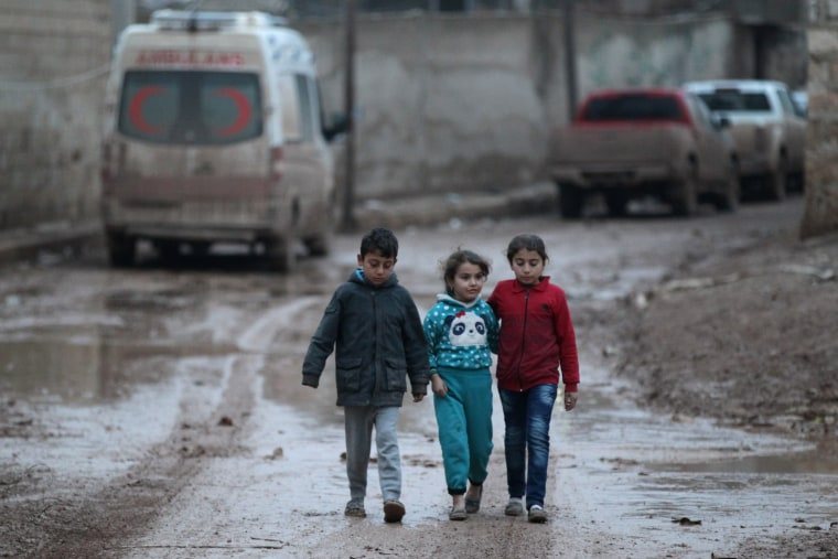 Image: Children walk near a parked ambulance in northern Aleppo, Syria