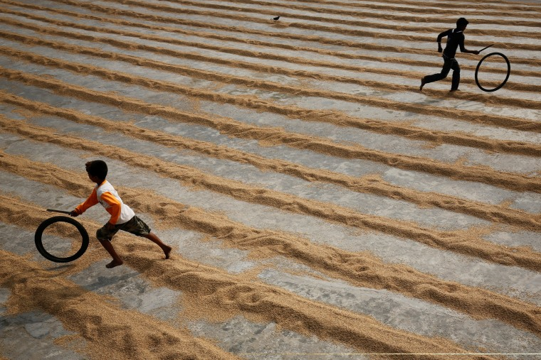 Image: Children play with bicycle tires at a rice-processing mill in Muktarpur