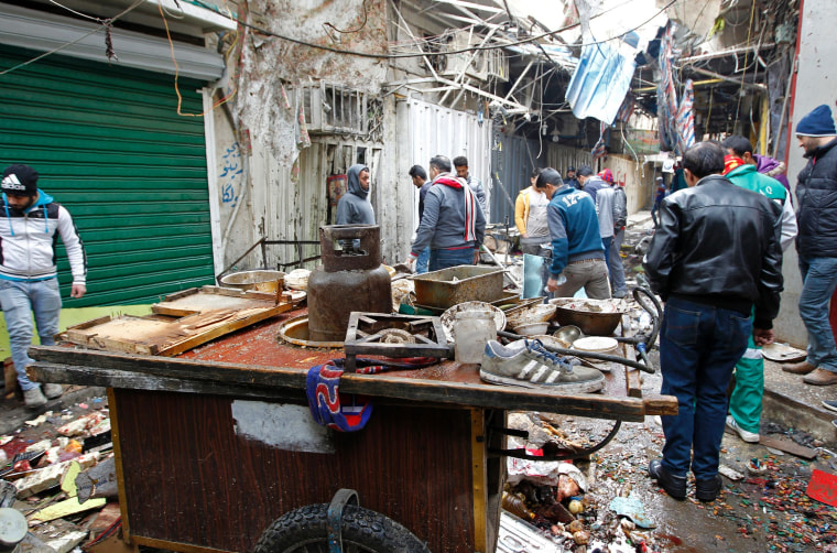 Image: Iraqis look at the aftermath following a double bomb attack in a busy market area in Baghdad.