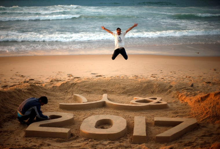 """Image: Palestinian artist Yazed Abu Jarad puts the final touches on a sand sculpture that reads \""""Welcome 2017\"""", as a man jumps, at a beach in the northern Gaza Strip"""