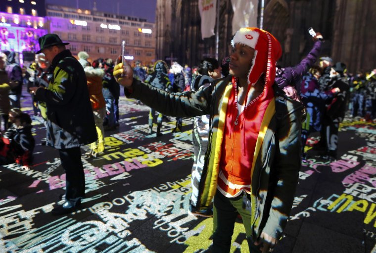 """Image: A refugee Joseph from Kenia takes a selfie during the laser installation \""""Time Drifts Cologne\"""" before New Year celebrations for 2017 in Cologne"""