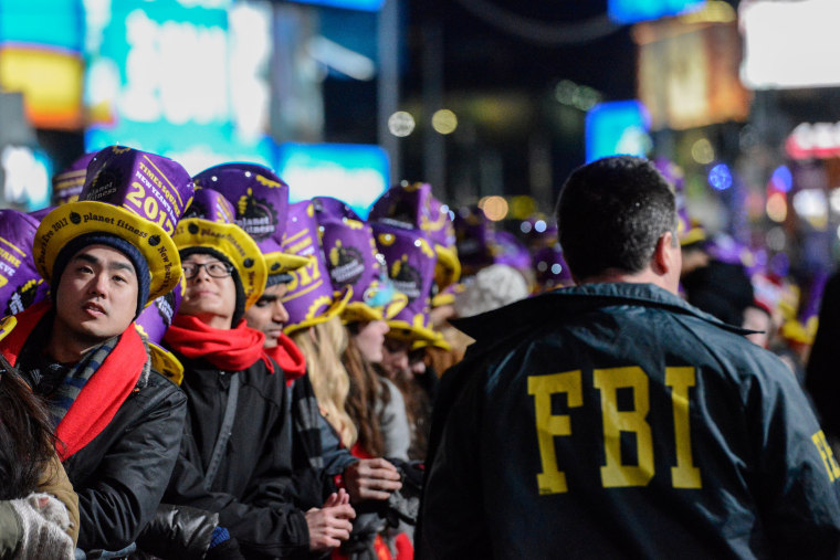 Image: An FBI agent walks past revelers gathered in Times Square on New Year's Eve in New York