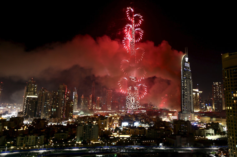Image: The Address Downtown Dubai hotel and residential block is seen engulfed by fire as fireworks explode over the Burj Khalifa, the tallest building in the world, during the New Year celebrations