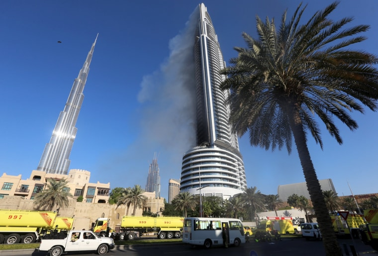 Image: Plumes of smoke rise from the 63-storey Address Downtown Dubai hotel and residential block near the Burj Khalifa in Dubai