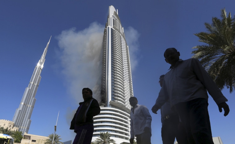 Image: People walk as plumes of smoke rise from the 63-storey Address Downtown Dubai hotel and residential block in Dubai