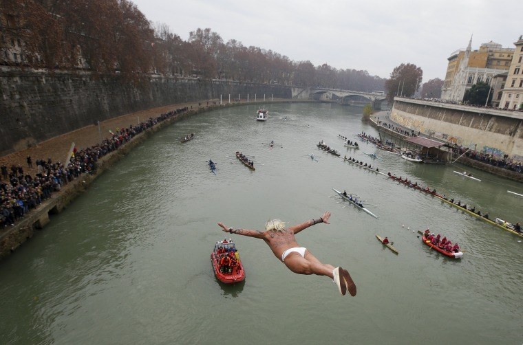 Image: Palmulli of Italy dives into the Tiber River from the Cavour bridge, as part of traditional New Year celebrations in Rome