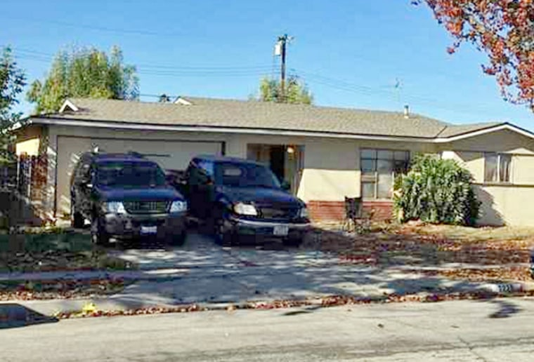 Vehicles are parked outside a home where Los Angeles County authorities say a man shot and killed his wife and two others on New Year's Eve before his son wrestled the gun away and fatally shot him in Rowland Heights, Calif.