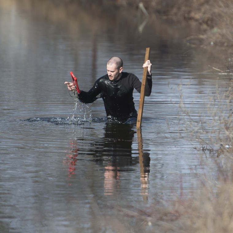 Thurmond Clark wades into the Lehigh Canal to search evidence to find Jayliel Vega Batista, a missing 5-year-old autistic boy who wandered off from a New Year's Eve party on Thursday night, while working in Allentown, Pa.