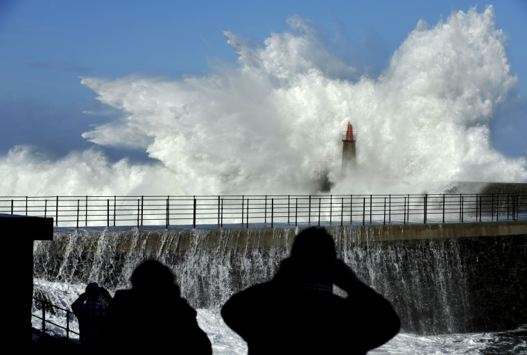 Image: People take pictures of huge waves crash on the Viavelez seafront in the northern Spanish region of Asturias