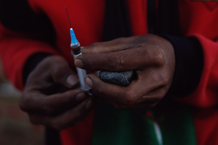Image: A miner holds in his hands a jade stone and a syringe to use heroin at a mine dump at a Hpakant jade mine in Kachin state