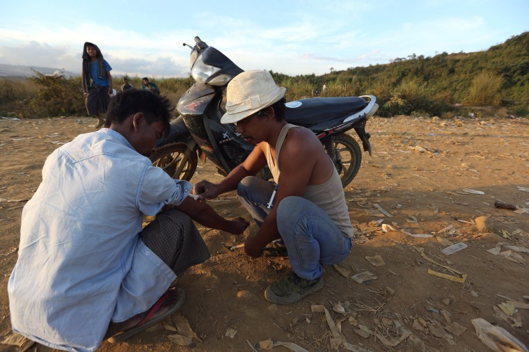 Image: Two miners inject heroin into each other at a mine dump at a Hpakant jade mine in Kachin state