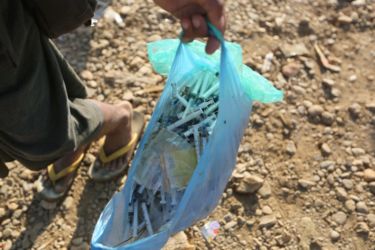 Image: A miner collects used syringes which miners used to inject heroin at a jade mine dump at a Hpakant in Kachin state