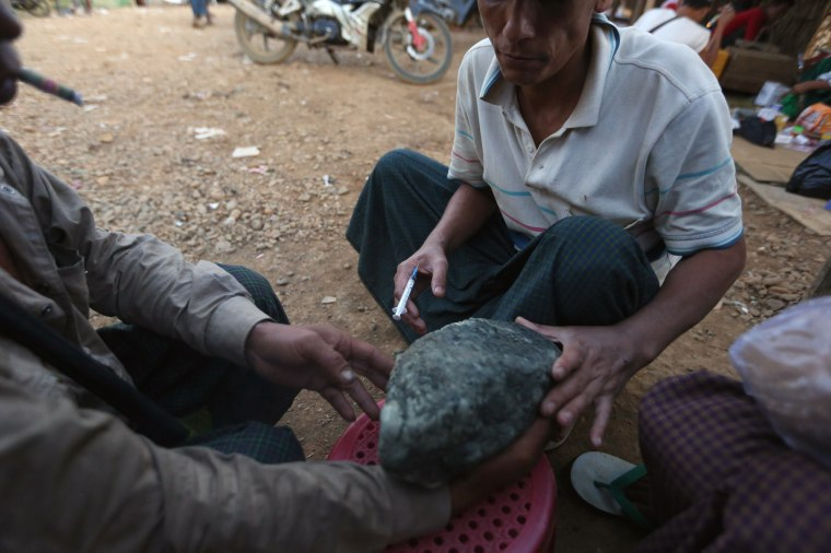 Image: Miners take a look at a jade stone while one of them injects himself heroin at a mine dump at a Hpakant jade mine in Kachin state