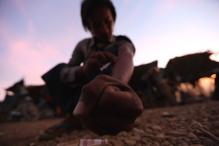 Image: A miner injects heroin at a mine dump at a Hpakant jade mine in Kachin state