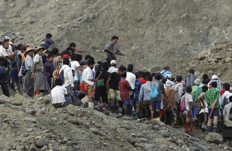 Image: Miners search for jade stones at a mine dump at a Hpakant jade mine in Kachin state