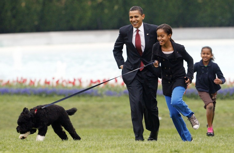 Malia Obama runs with Bo, followed by her dad and sister, Sasha, on the South Lawn of the White House on April 14, 2009.