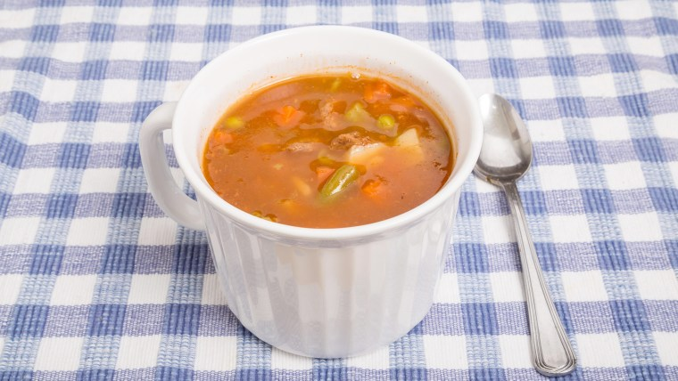 A hot mug of beef and vegetable soup