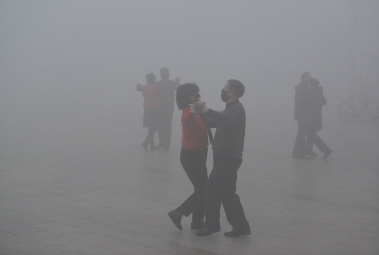Image: People wearing masks dance at a square among heavy smog during a polluted day in Fuyang