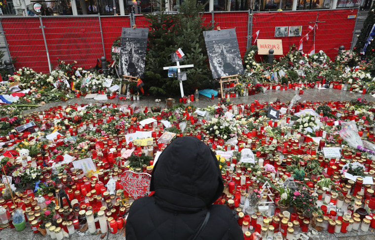 Image: A visitor looks at a memorial to victims of the December 19 terror attack at a Chrismas market