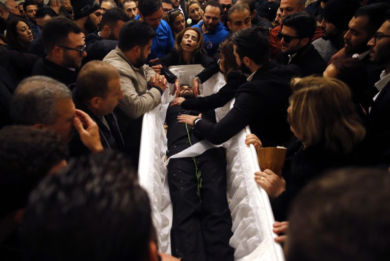 Image: Relatives and friends of Elias Wardini mourn over his coffin