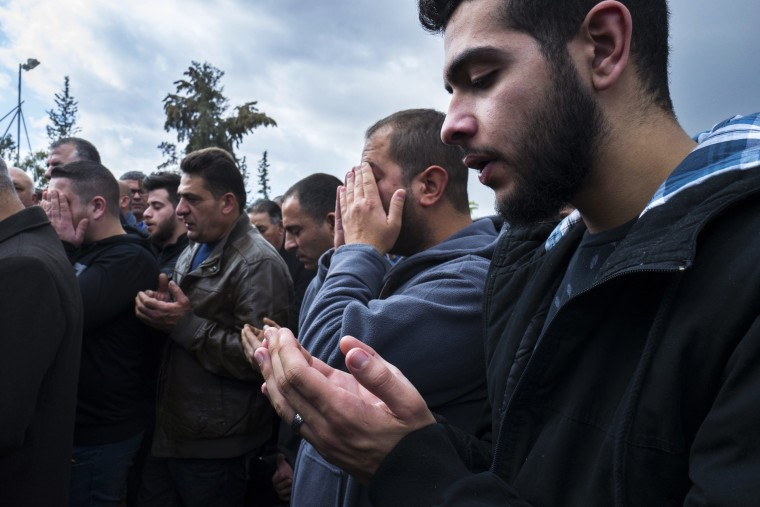 Image: Family members and friends pray at the grave of Layan Nasser, an 18-year-old Israeli Arab woman, during her funeral in the town of Tira, north east of Tel Aviv on Jan. 3, 2017.