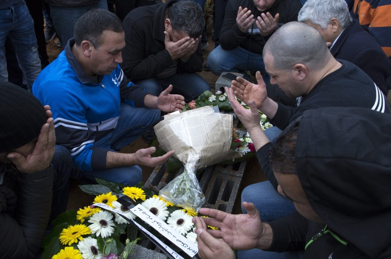 Image: Family members pray over the grave of Layan Nasser, an 18-year-old Israeli Arab woman, during her funeral in the town of Tira, north east of Tel Aviv on Jan. 3, 2017.