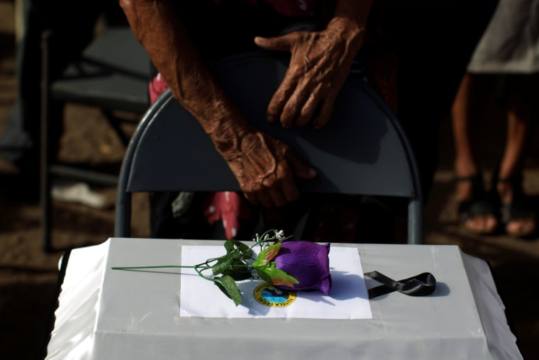 People observe the remains of their relatives as they participate in a ceremony to commemorate the 35th anniversary of the El Mozote massacre in El Mozote