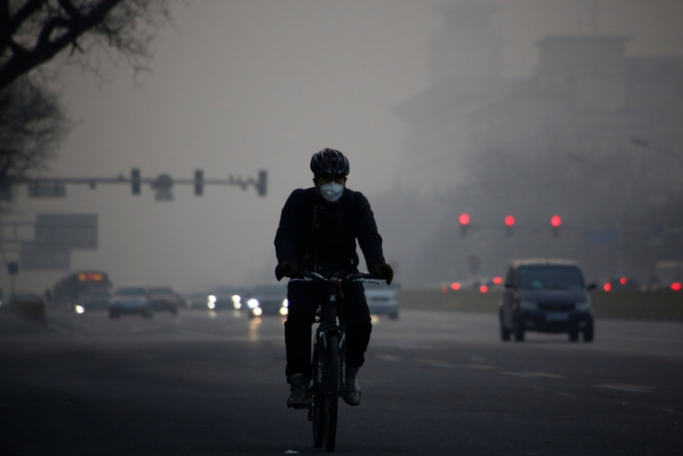 Image: A cyclist wears a face mask on a polluted day in Beijing