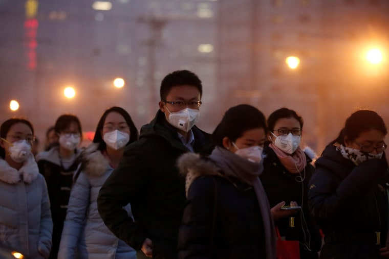 Image: People wear face masks as they cross a street on a polluted day in Beijing