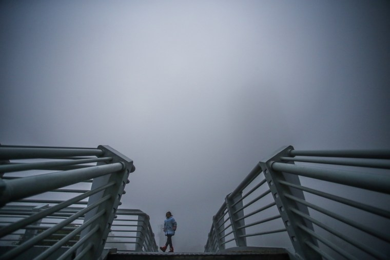 Image: A girl walks among heavy smog on a bridge in Hefei