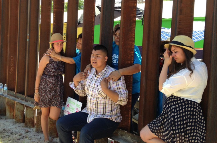 """Evelyn Rivera, left, Carlos Padilla, front center, and Renata Teodoro, right, reunite with their mothers on opposite sides of the border wall that divides Nogales, Arizona from Nogales, Mexico, on June 11, 2013. The youth, who were born in Mexico and brought to the U.S. as children, traveled from Seattle, Miami and Boston to meet at the border fence with their mothers who they had not seen in years. The four are """"dreamers,"""" youth whose families entered the country without authorization when they were children."""