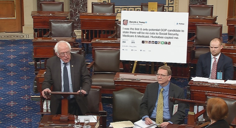 Image: Senator Bernie Sanders addresses the Senate floor while displaying a poster of a tweet by Donald Trump