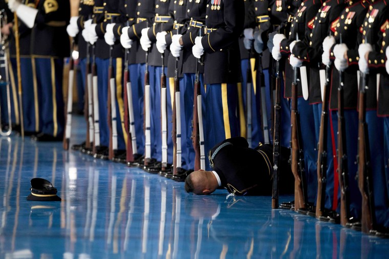 Image: A member of the US Army Honor Guard lays on the floor after passing out during an Armed Forces Full Honor Farewell Review for President Barack Obama at Joint Base Myer-Henderson in Arlington, Virginia on Jan.4, 2017.