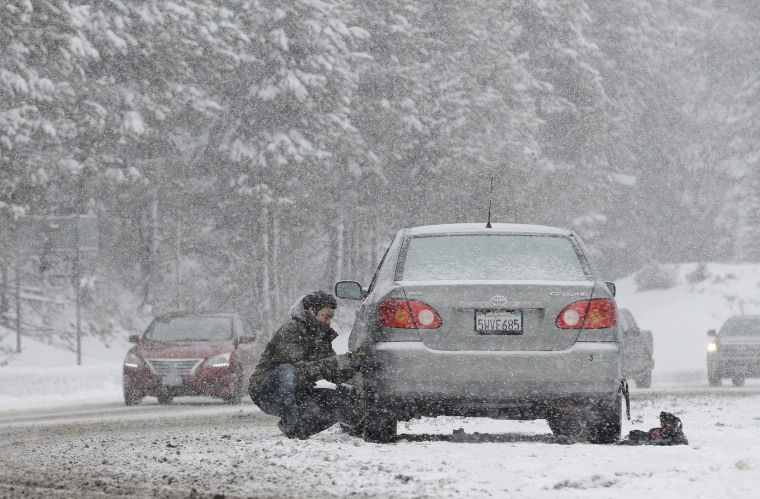 Image: A motorist puts on snow chains near Echo Summit, Calif.