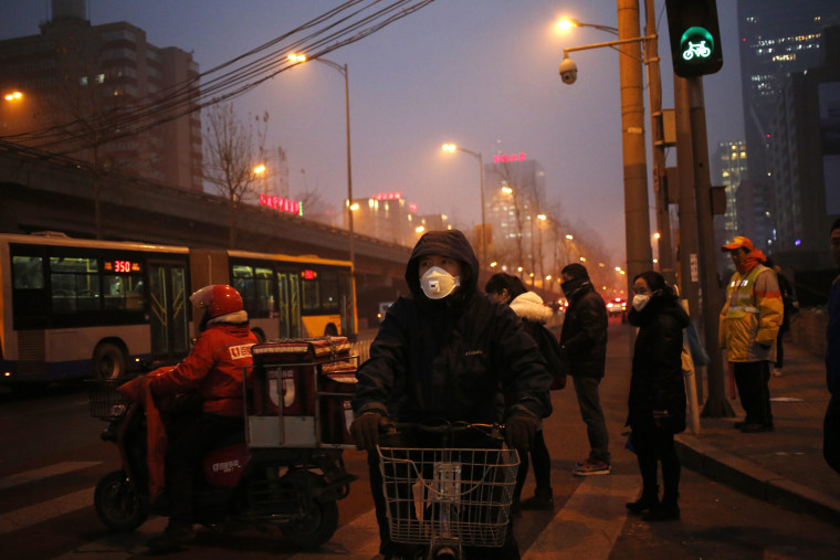 Image: Bicycle riders wearing masks wait during heavy traffic on a smoggy day in Beijing, China on Jan. 4.