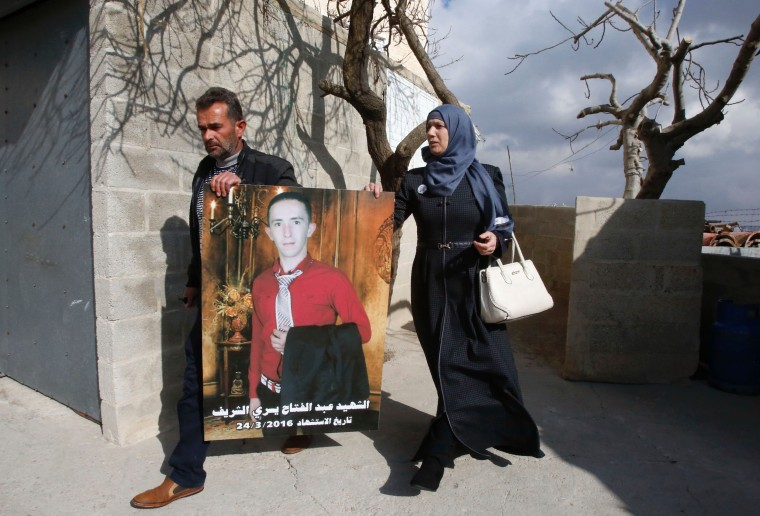 Image: Rajaa and Yousri, the mother and father of Abdul Fatah al-Sharif (seen in the portrait), head out into the streets in the West Bank town of Hebron on Jan. 4 after watching on television the verdict of the trial of Israeli soldier Elor Azaria who ki
