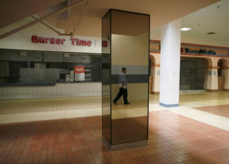 A man walks past empty stores in the deserted Carousel shopping mall in San Bernardino