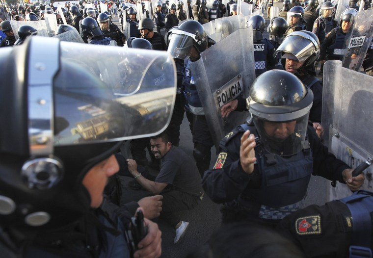Image: Police forcibly remove demonstrators who blocked a main road for about an hour as they protest hikes in gas prices in Mexico City on Jan. 4.