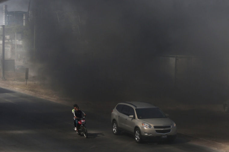 Image: Vehicles pass through a cloud of smoke as tires burn during a protest against the rising prices of gasoline enforced by the Mexican government, at the side of a Pemex gas station in San Miguel Totolcingo, Mexico on Jan. 3.