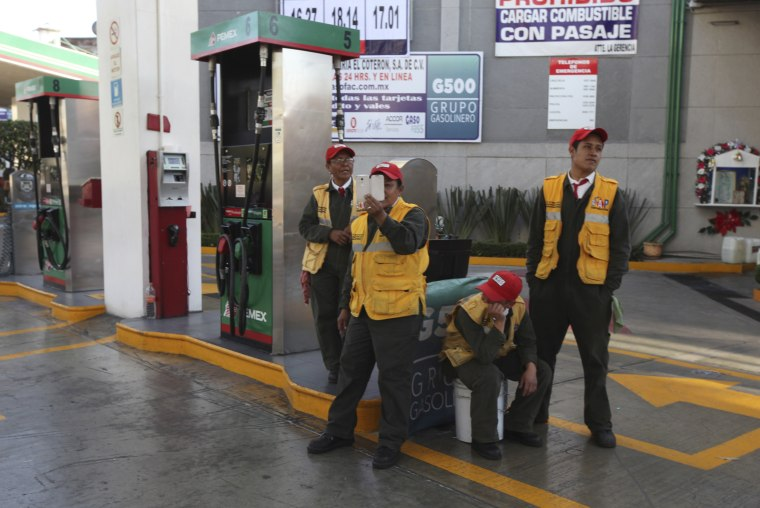 Image: A gas station attendant films demonstrators blocking a main road for about an hour as they protest hikes in gas prices in Mexico City on Jan. 4.