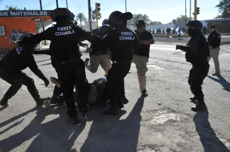 Image: Policemen kick a demonstrator on the floor during a protest against the rising prices of gasoline enforced by the Mexican government, in Monclova